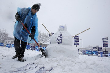 A worker builds a snow man of Democratic presidential candidate Bernie Sanders during a snow storm in Manchester