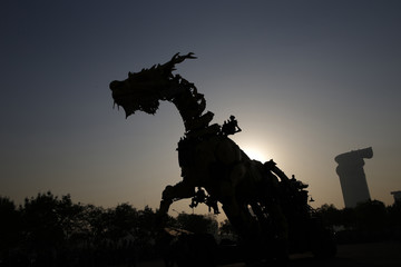 """A silhouette of a mechanical installation named """"Long Ma"""" and its operators are seen as it makes way during the Long Ma performance in front of the National Stadium, also known as the Bird's Nest, in Beijing"""
