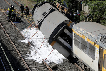 Firefighters work at the scene of a train that derailed in Galicia in north-western Spain