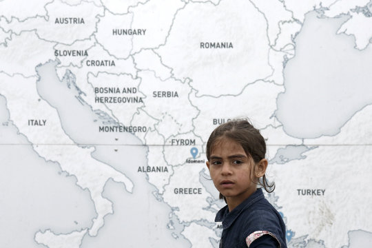 A girl walks past a map illustrating part of Europe, at a makeshift camp for refugees and migrants at the Greek-Macedonian border near the village of Idomeni