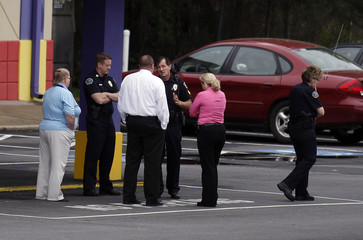 Cobb County police talk to people at a staging area at a skating rink after a shooting at a FedEX Corp facility at an airport in Kennesaw