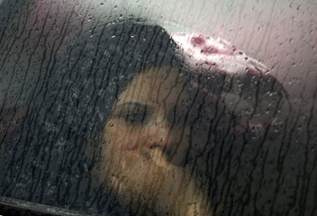 A Tunisian woman is seen through the window of her husband's car as she and her family cross in Tunisia at the Ras Jdir border crossing to flee the unrest in Libya