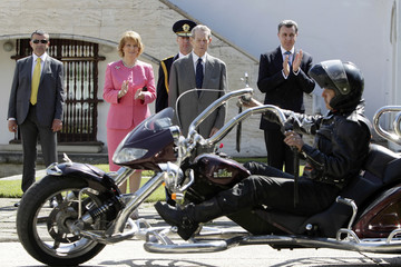 Romania's former King Michael, his daughter Princess Margarita and Prince consort Radu look at a biker in Bucharest