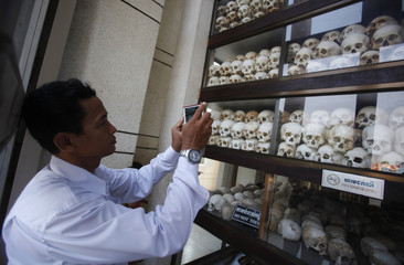"""A man takes pictures of skulls and bones of more than 8,000 victims of the Khmer Rouge regime at Choeung Ek, a """"Killing Fields"""" site located on the outskirts of Phnom Penh"""