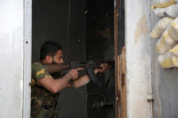 Free Syrian Army fighter fires weapon during clashes with forces loyal to President Assad in old city of Aleppo