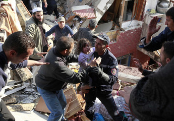 An Algerian rescuer evacuates a baby from the scene after a gas explosion at Oued Koreiche neighbourhood in Algiers