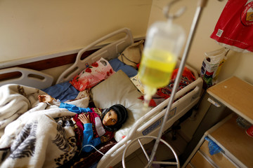 A girl lies on a bed at a cancer treatment center in Sanaa