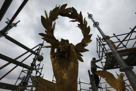 Laurel wreath of the statue atop the Siegessaeule victory column is silhouetted against the sky as worker climbs scaffolding in Berlin