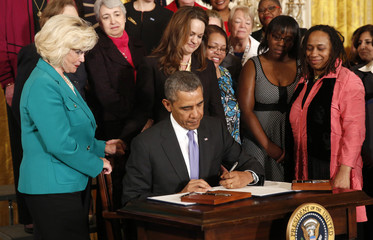 Obama holds signs executive actions aimed at equal pay for women at the White House in Washington