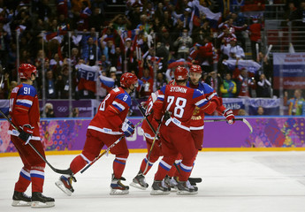 Russia's Kovalchuk is congratulated by teammates after scoring the game winner on his team's second shootout attempt against Slovakia during their men's preliminary round ice hockey game at the Sochi 2014 Winter Olympic Games