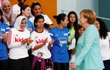"""German Chancellor Merkel stands in front of international female soccer players of the """"Discover Football"""" project before taking a group picture at the chancellery in Berlin"""
