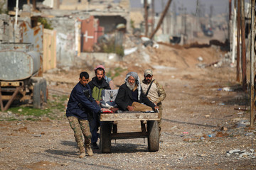 Displaced Iraqi men, who fled the Islamic State stronghold of Mosul, and Iraqi security forces push an elderly man in a cart at Intisar district of eastern Mosul