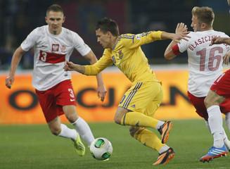 Ukraine's Konoplyanka is challenged by Poland's Jedrzejczyk and Blaszczykowski during their 2014 World Cup qualifying soccer match in Kharkiv