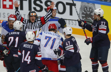 Official intervenes in a scuffle between players of Russia and the U.S. during their Ice Hockey World Championship semifinal game at the O2 arena in Prague