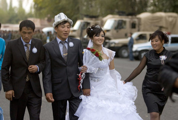 A newly wed couple walks, with military cars in the background, on a street in the city of Osh