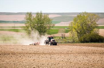 Tractor Working in Dusty Field