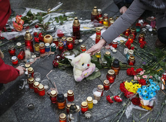 A woman lays a toy during a rally in memory of people who died during shelling in the southern Ukrainian city of Mariupol on Saturday, in Kiev