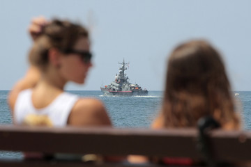 People spend time at a quay, with a Russian warship seen in the background, in Sevastopol in Crimea