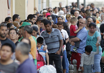 People line up to receive bags of food delivered by volunteers of the Banco de Alimentos in Valencia
