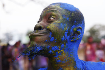 A man smeared with coloured powdered called abeer makes a funny face during Phagwa celebrations in Arranguez