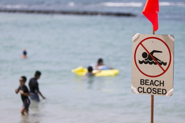 A warning sign stating that the beach is closed is pictured at Waikiki Beach in Honolulu, Hawaii