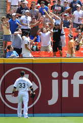 Marlins Scott Cousins watches fans try to catch a home run ball hit by Mets Willie Harris during the first inning of their MLB baseball game in Miami