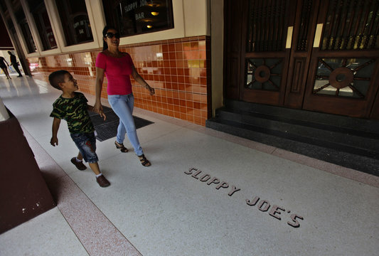 A woman and child walk beside the entrance of newly reopened Sloppy Joe's bar in Havana