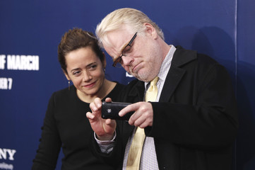 Cast member Philip Seymour Hoffman arrives with Mimi O'Donnell at the premiere of Ides of March in New York