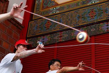 Members of the Sanxia Pinpoint Spinning Top Team throw spinning tops simultaneously at Sanxia old street in New Taipei City, Taiwan