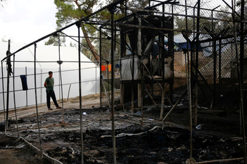 A migrant stands next to a burned tent at the Moria migrant camp, after a fire at the facility, on the island of Lesbos