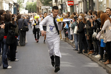 Waiters carrying trays take part in a race in Paris