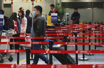 A man wearing a mask walks toward a ticketing desk during a hazy day at an airport terminal in Beijing