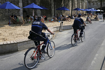 """French municipal police on bikes patrol along the banks of the Seine during """"Paris plages"""" event  in Paris"""