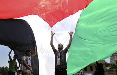 Palestinians hold a large Palestinian flag during a rally ahead of the 66th anniversary of Nakba in Gaza City