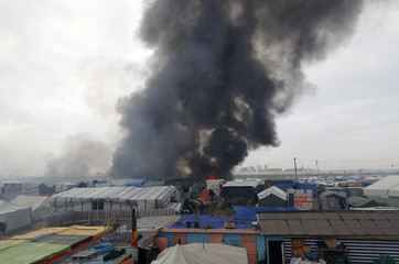 """Smoke rises the sky as makeshift shelters and tents burn in the """"Jungle"""" on the third day of the evacuation of migrants as part of the dismantlement of the camp called the """"Jungle"""" in Calais"""