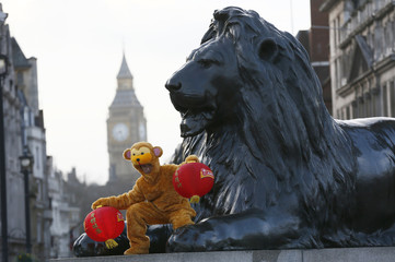 A performer in a monkey costume poses during a photo call to welcome in the Chinese New Year of the Monkey in Trafalgar Square