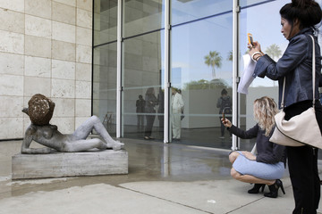 "Visitors photograph ""Untilled (Liegender Frauenakt),"" a concrete figure with a wax beehive and live bees, during a press preview of French artist Pierre Huyghe's first major retrospective at the Los Angeles County Museum of Art"