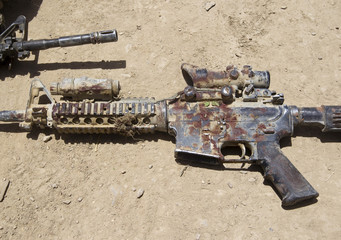 The blood-covered M4 rifle of a U.S. Army soldier wounded by an IED lies on a ground in southern Afghanistan