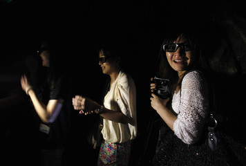 """Visitors react while watching a projection with 3D glasses inside a """"5D haunted house"""" at Hong Kong Ocean Park"""