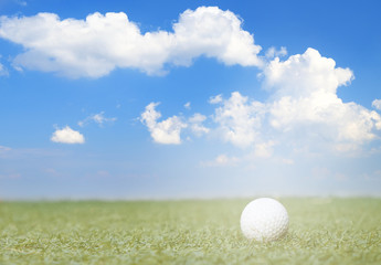 golf ball on fake green grass with sunlight and cloud blue sky background.