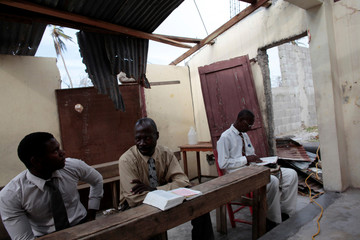 Men attend to a religious service in a church after Hurricane Matthew in Les Cayes, Haiti