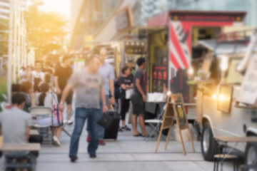 Abstract blurred background customer looking menu by food trucks carnival.
