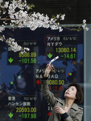 A woman takes a photo of cherry blossoms with her mobile phone in front of an electronic board displaying market indices around the world in Tokyo