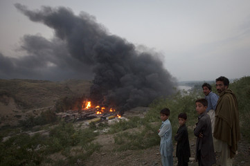 Residents watch from a hill top as smoke rises from burning fuel tankers near Nowshera, Pakistan