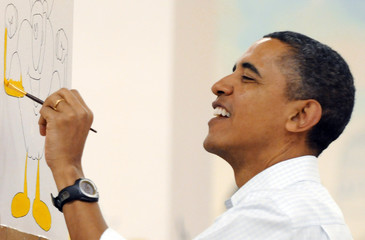 Obama paints a cartoon apple at Stuart-Hobson Middle School on Capitol Hill in Washington
