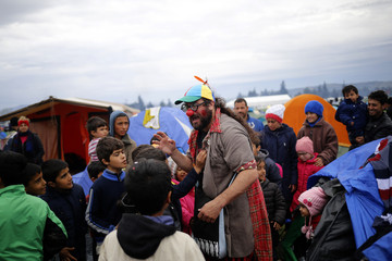 A clown entertains migrant children at a makeshift camp on the Greek-Macedonian border, near the village of Idomeni