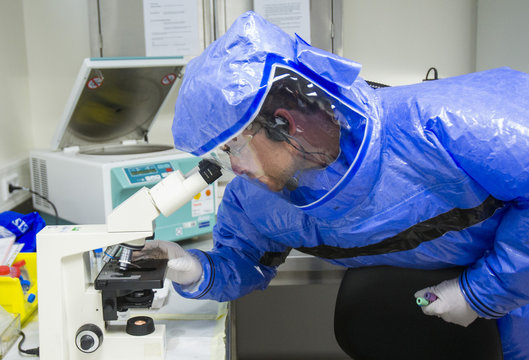 Physician looks through microscope at quarantine station for patients with infectious diseases in Berlin