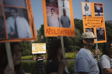 A woman holds up a sign during a protest against indefinite solitary confinement in California prisons, in Sacramento