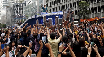 Fans use their mobile phones to take pictures of Miss Universe 2015 Pia Alonzo Wurtzbach as her motorcade passes along Ayala Avenue in  Makati
