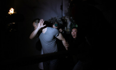 Visitors react as an artist performs at the Shanghai Nightmare haunted house attraction in Shanghai